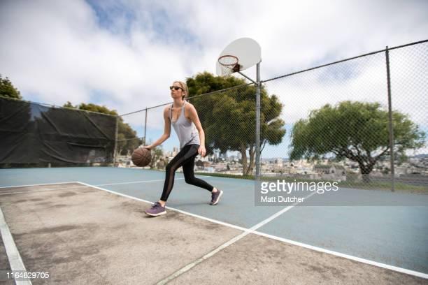 young woman playing basketball - ドリブル ストックフォトと画像