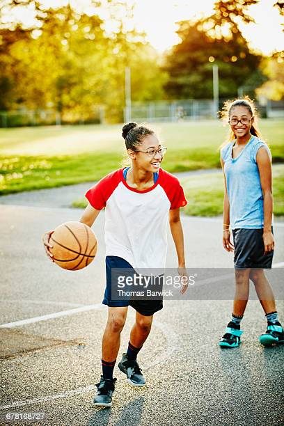 Young woman playing basketball with sister