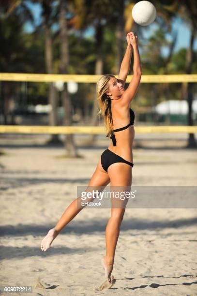 Young woman playing beach volleyball in bikini