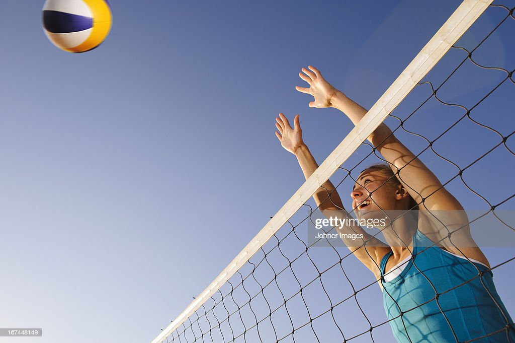 Young woman playing beach volleyball : Stock Photo