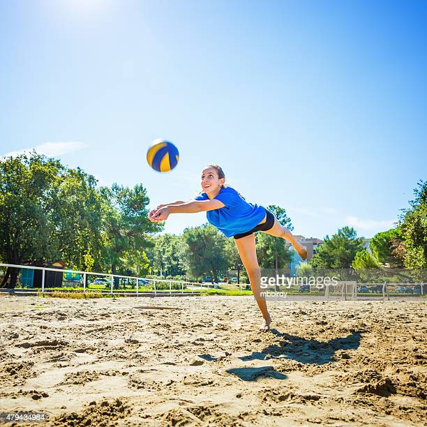 Young woman playing beach volleyball