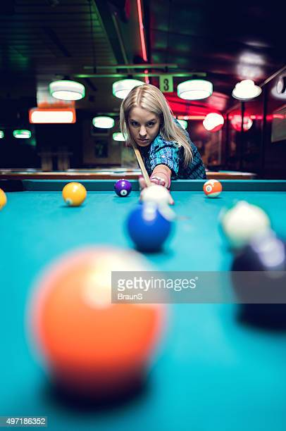 Young woman playing billiard in a pool hall.