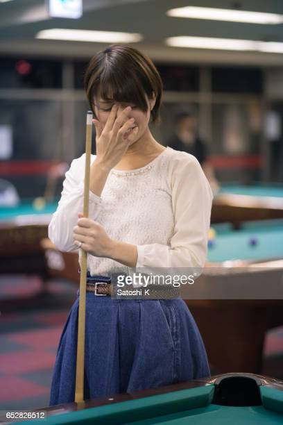 Young woman playing billiards - miss shot