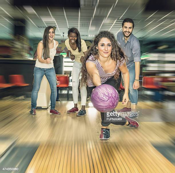 Young woman playing bowling with friends
