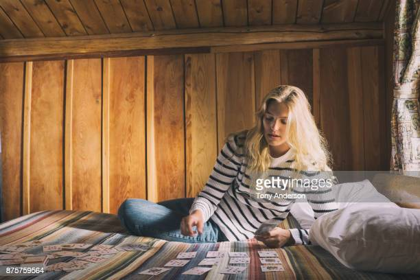 Young woman playing cards on bed in rustic cabin
