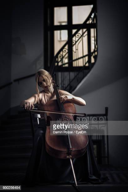 young woman playing cello at home - musiker stock-fotos und bilder
