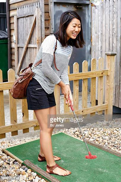Young woman playing crazy golf