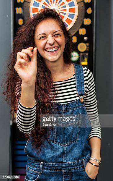 young woman playing darts in a pub - darts stockfoto's en -beelden