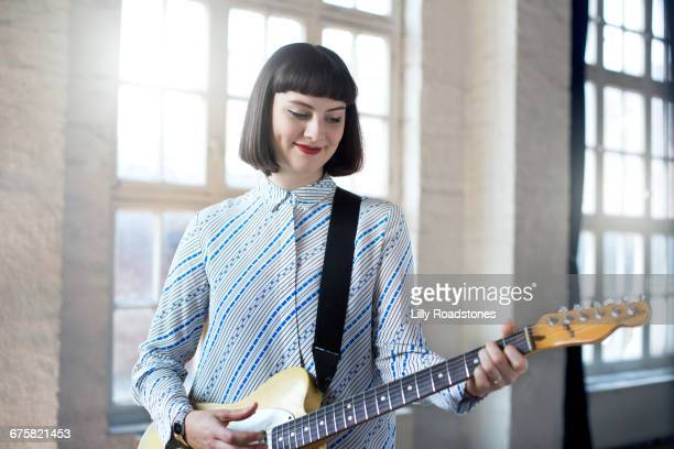 young woman playing electric guitar in studio - ベースギター ストックフォトと画像