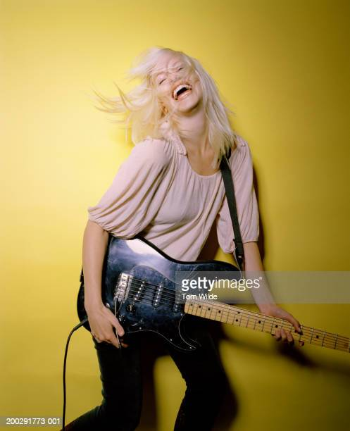 Young woman playing electric guitar throwing head back, laughing