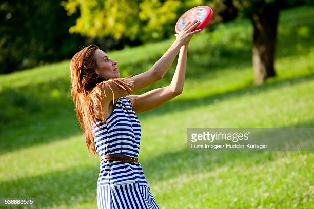 Young woman playing frisbee outdoors