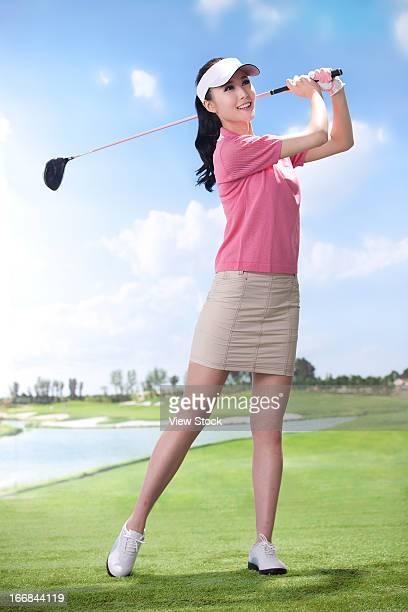 Young woman playing glof