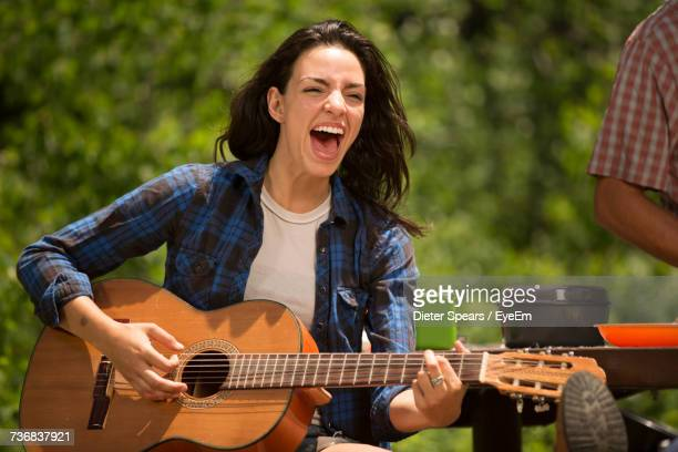 Young Woman Playing Guitar And Singing Outdoors On Sunny Day