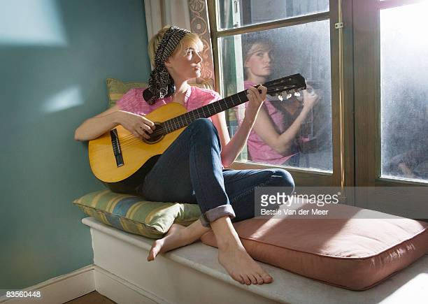 Young woman playing guitar at home.