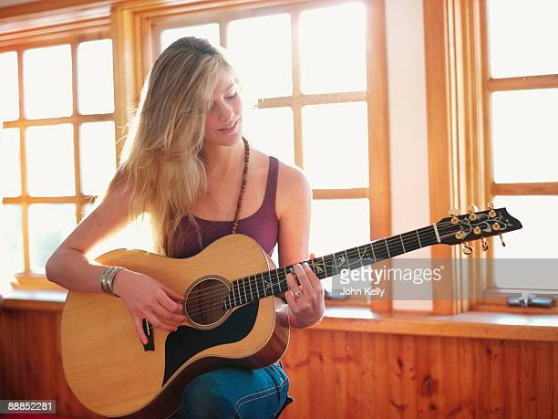 young woman playing guitar at home - acoustic guitar stock pictures, royalty-free photos & images