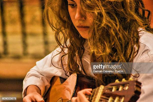 Young Woman Playing Guitar In Concert