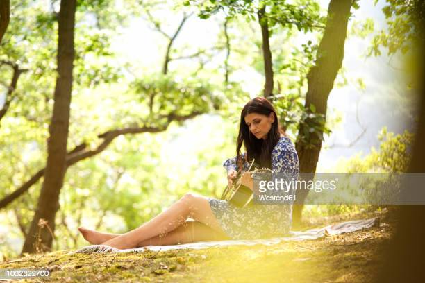 young woman playing guitar in forest - シンガーソングライター ストックフォトと画像