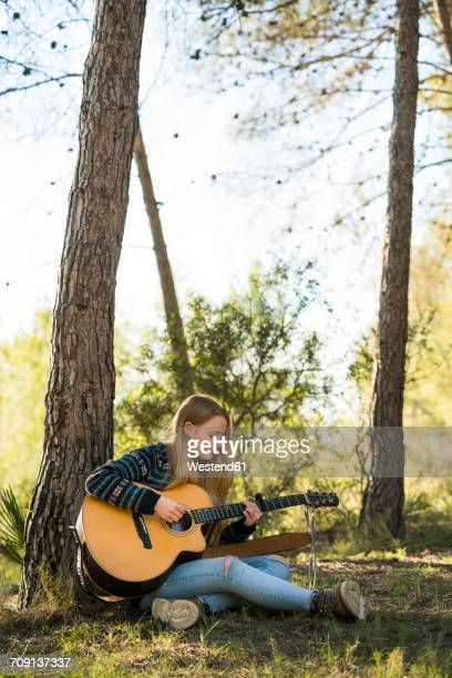 young woman playing guitar in nature - singer songwriter stock pictures, royalty-free photos & images
