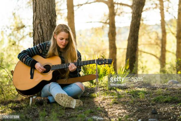 young woman playing guitar in nature - classical guitar stock photos and pictures