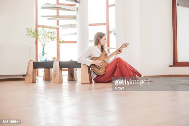 Young Woman Playing Guitar in the New Home