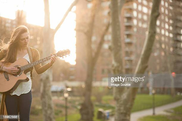 Young woman playing guitar in the park