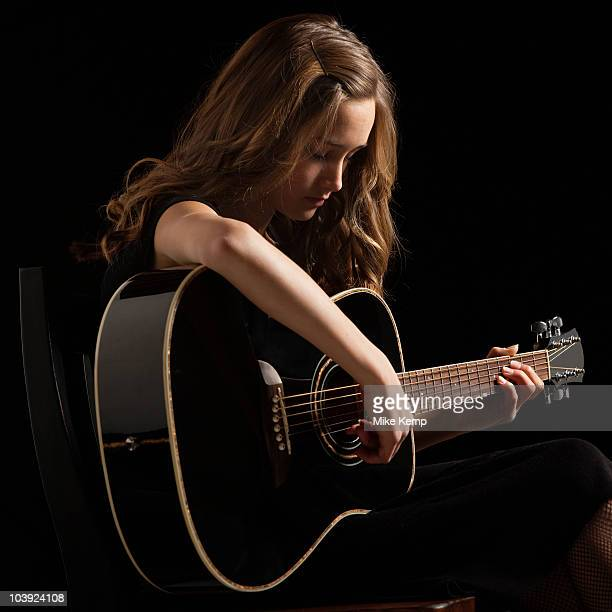young woman playing guitar - pre adolescent child stock pictures, royalty-free photos & images