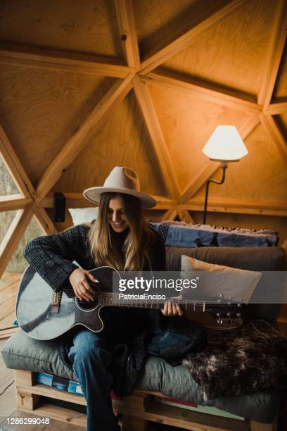 young woman playing guitar - singer songwriter stock pictures, royalty-free photos & images