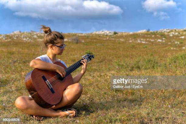 Young Woman Playing Guitar While Sitting On Field