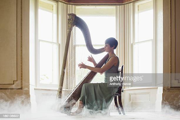 Young woman playing harp indoors with misty floor