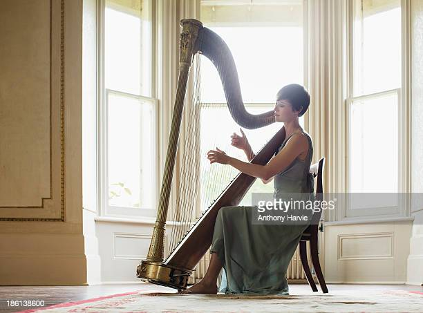 young woman playing harp - evening gown stock pictures, royalty-free photos & images