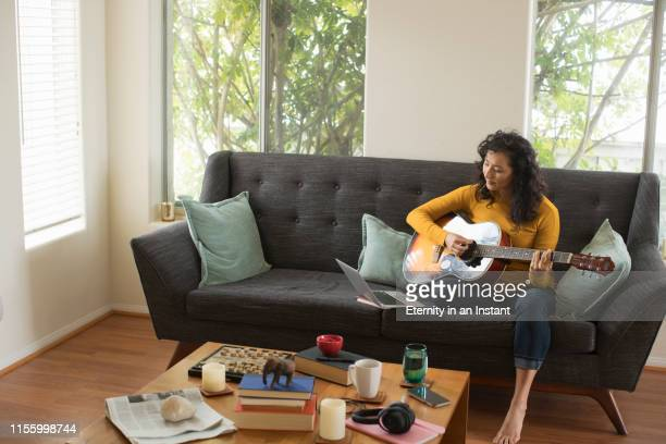 young woman playing her guitar at home - guitar stock pictures, royalty-free photos & images