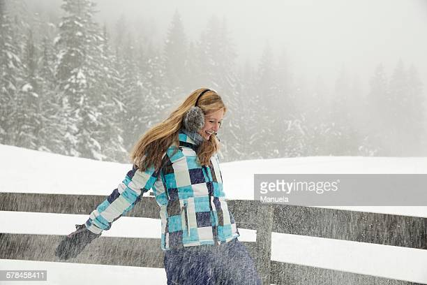 Young woman playing in snow, Sattelbergalm, Tirol, Austria