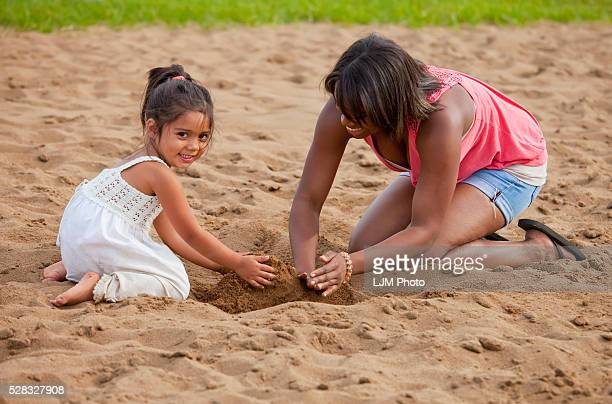 Young Woman Playing In The Sand With A Toddler; Edmonton Alberta Canada