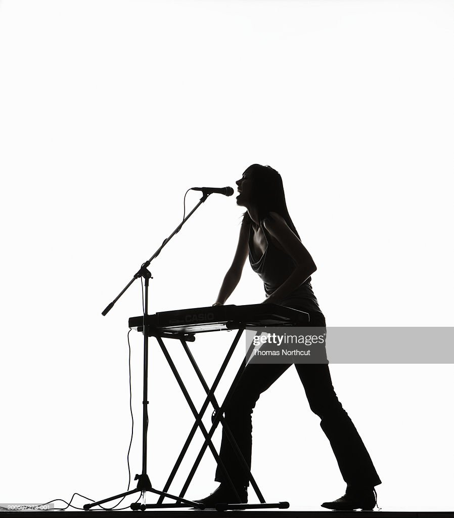 Young woman playing keyboard and singing into microphone, side view : Stock Photo