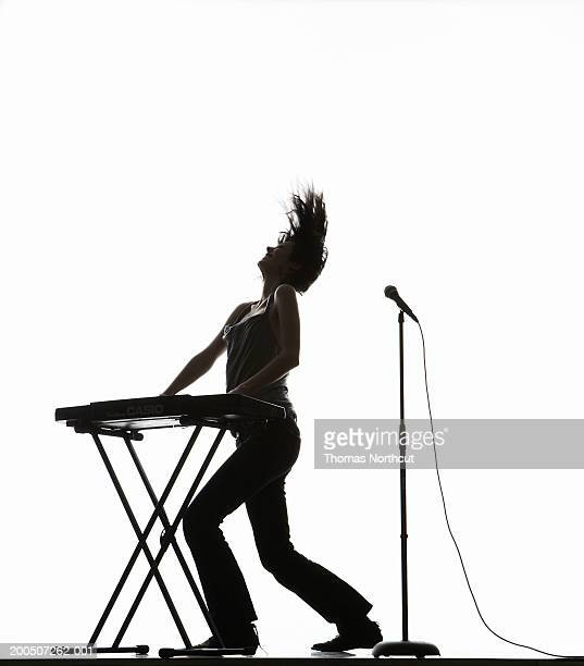 young woman playing keyboard and tossing hair, side view - keyboard player stock photos and pictures