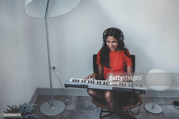 young woman playing keyboard at home - keyboard player stock photos and pictures