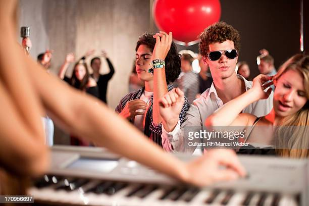 Young woman playing keyboard in nightclub