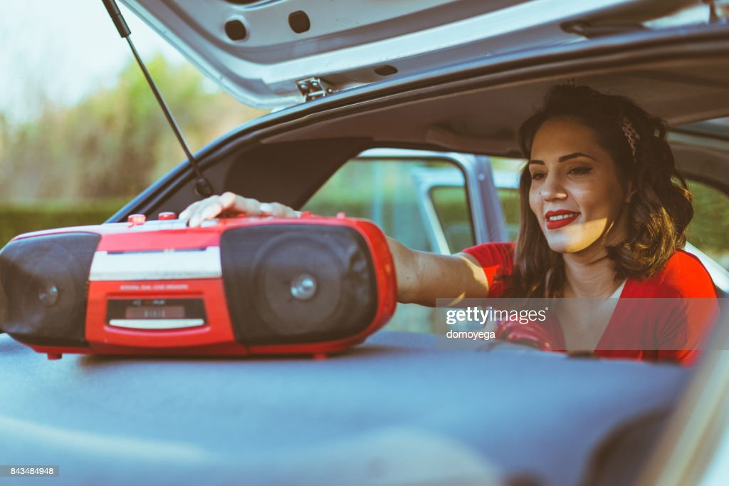 Young woman playing music on a boom box from a car : Stock Photo