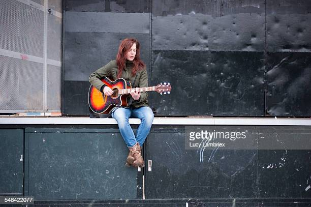 Young woman playing music on outdoors stage