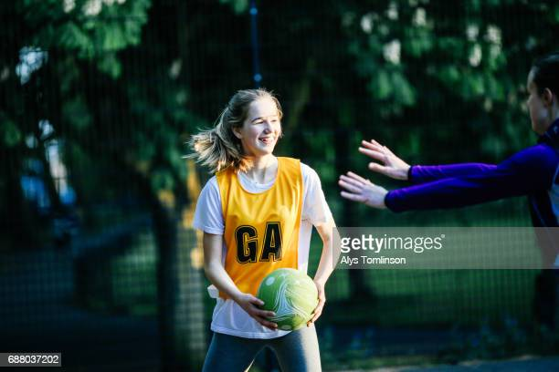young woman playing netball and being marked on outdoor court in city park