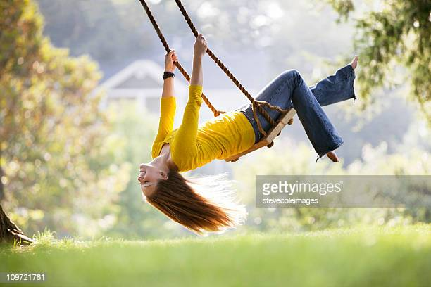 young woman playing on a swing - swinging stock pictures, royalty-free photos & images