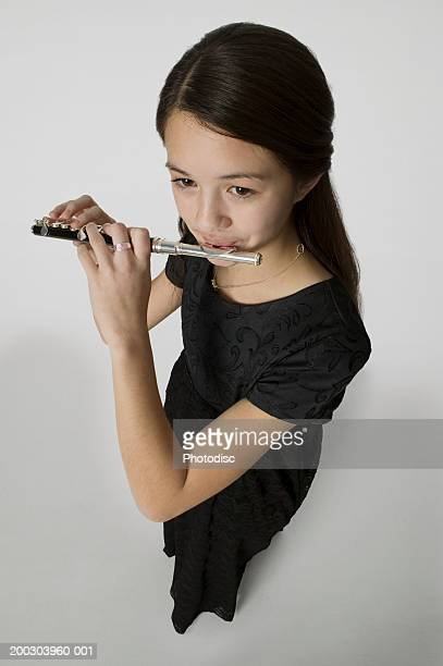 Young woman playing piccolo in studio, elevated view