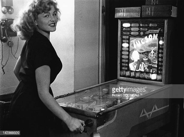 A young woman playing pinball in the Mayol's bar on October 6 1953 in Paris France