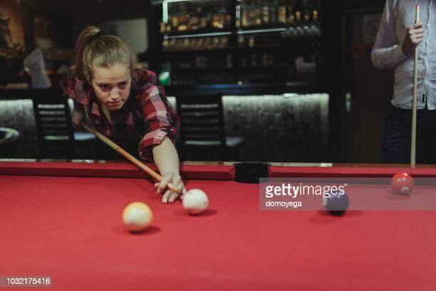 junge frau spielen billard in der bar - poolbillard billard stock-fotos und bilder
