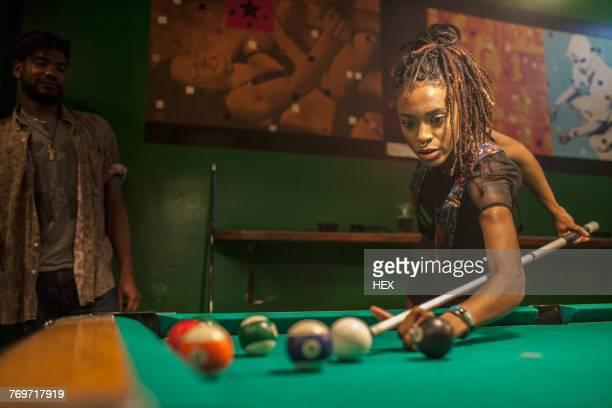 a young woman playing pool. - poolbillard billard stock-fotos und bilder