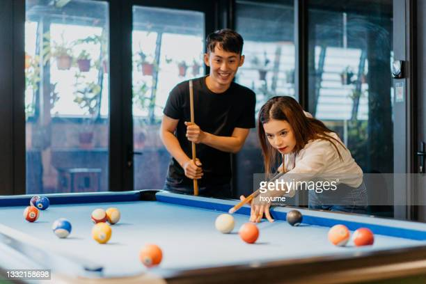 young woman playing pool with colleague in office game room - friendly match stock pictures, royalty-free photos & images