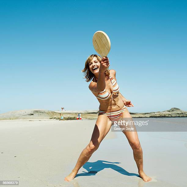 young woman playing racket ball on the beach