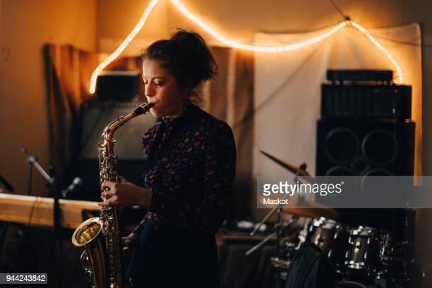 Young woman playing saxophone while rehearsing at illuminated studio