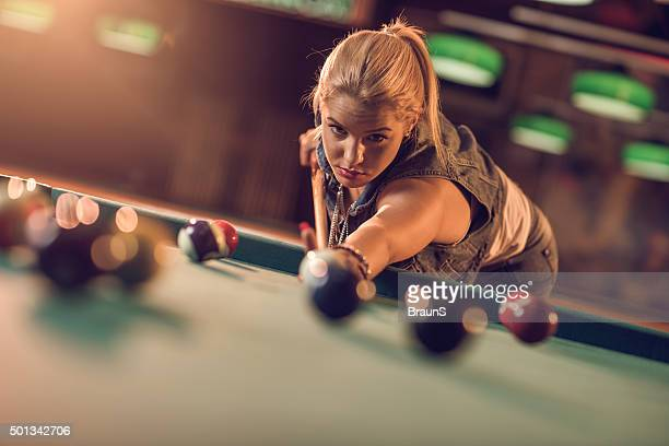 Young woman playing snooker in a pool hall.