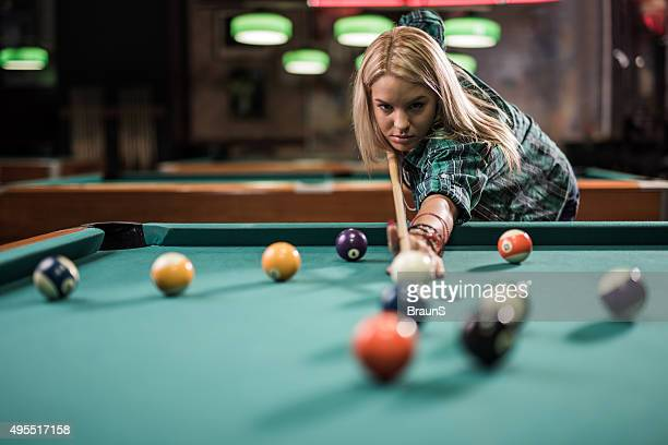 Young woman playing snooker in a pub.